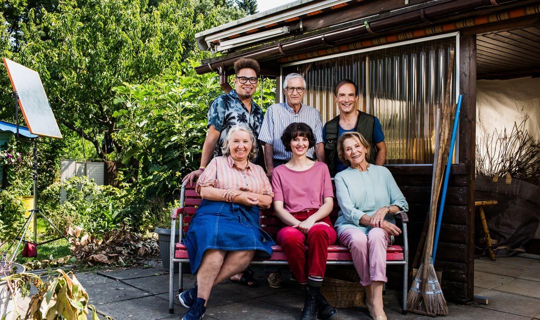 Der Cast des Schweizer FIlms Eden Einfach sitzt auf einer Bank im Garten